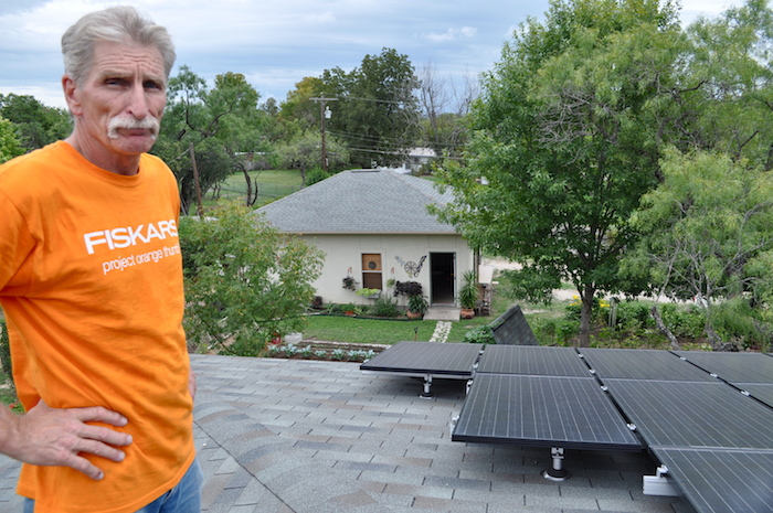 Ralph Talbott stands with his rooftop solar panel array in San Antonio. Photo by Iris Dimmick.