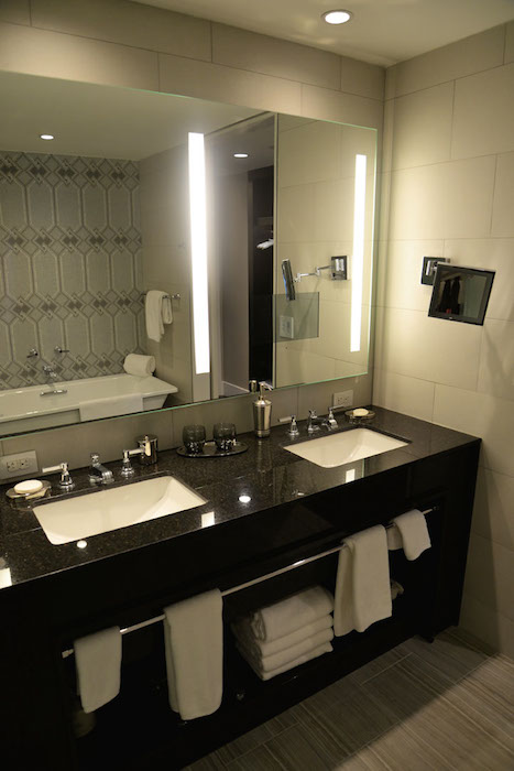 A bathroom in one of the model room displays at the St. Anthony Hotel. The new bathrooms feature soaking tubs, walk-in showers and double vanities. Photo by Annette Crawford.