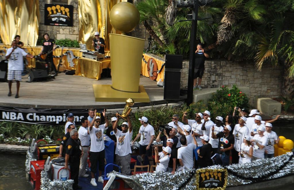Spurs Tony Parker, Boris Diaw, and friends hold high the Spurs' fifth NBA Championship trophy at the start of the 2014 Spurs Championship River Parade on June 30, 2014. Photo by Iris Dimmick.