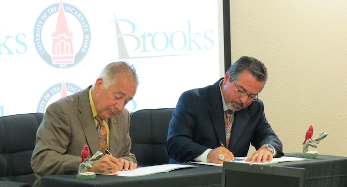 UIW President Louis Agnese Jr. (left) and Brooks City Base President and CEO Leo Gomez sign an agreement for BCB to host UIW's new medical school June 10, 2014. Photo by Erin Hood.