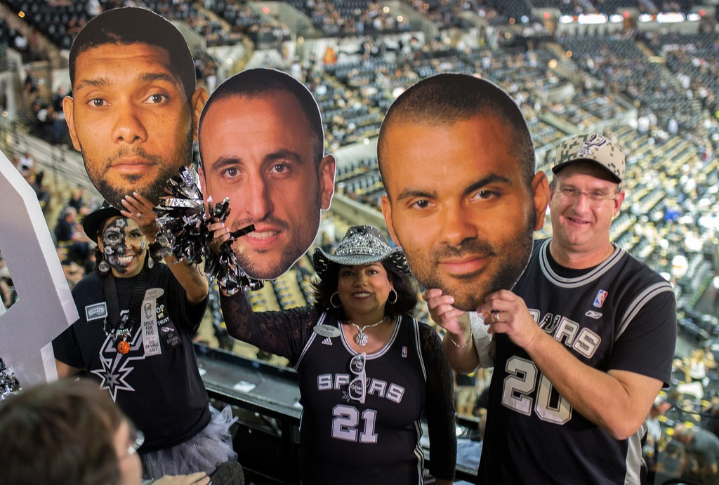 """Baseline Bums (from left) Brenda Flores, Bonnie Keammerer, and Nick Lockard hold up faces of """"The Big Three"""" Tim Duncan, Manu Ginobili, and Tony Parker during Game 1 of the 2014 NBA Finals. Photo by Scott Ball."""