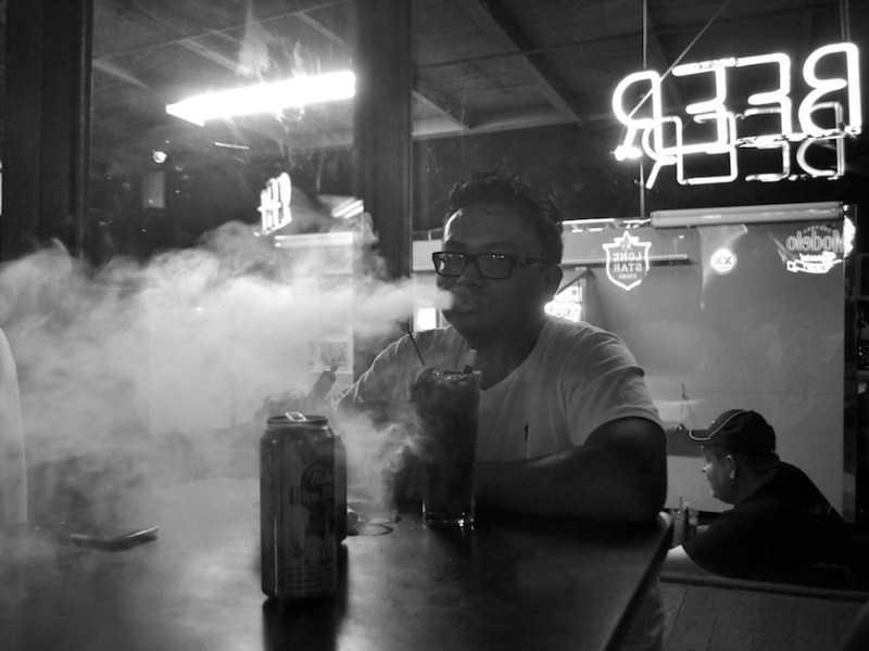 Devin Keo vapes at Bar America while watching the San Antonio Spurs win Game 4 of the 2014 NBA Finals. He went from smoking two to three packs of cigarettes a day to only four per week in addition to his vaporizor. Photo by Iris Dimmick.
