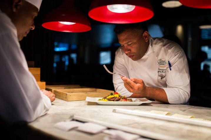 Executive Chef Geronimo Lopez -Monascal tastes a dish prepared by Nao staff. Photo by Scott Ball.