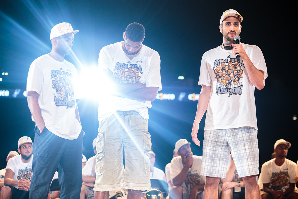 Spurs Manu Ginóbili speaks to the crowd while Tony Parker and Tim Duncan look on during the Spurs celebration at the Alamodome of their 2014 NBA Finals victory. Photo by Scott Ball.