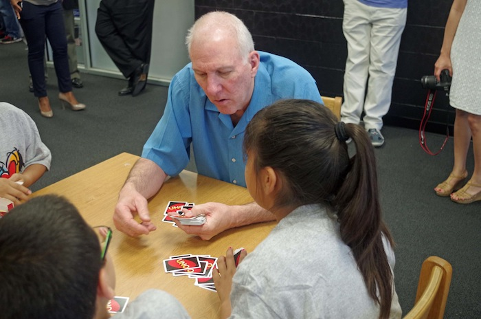 Spurs Coach Greg Popovich plays cards with Bowden Elementary School students after a press conference announcing a new NBA-sponsored Learn and Play Center at the school on June 6, 2014. Photo by Juan Garcia.