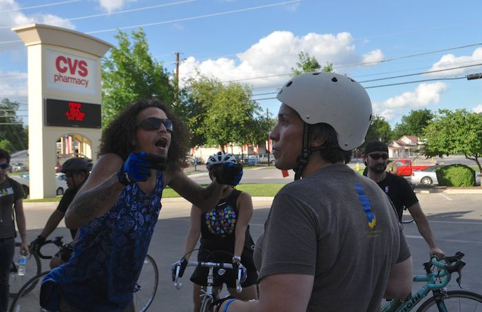 """Nicholas Duran (left) and Monica Walker (right) debate the use of bike lanes during the South Flores Street lane removal protest, """"Every Lane is a Bike Lane."""" June 4, 2014. Photo by Iris Dimmick."""