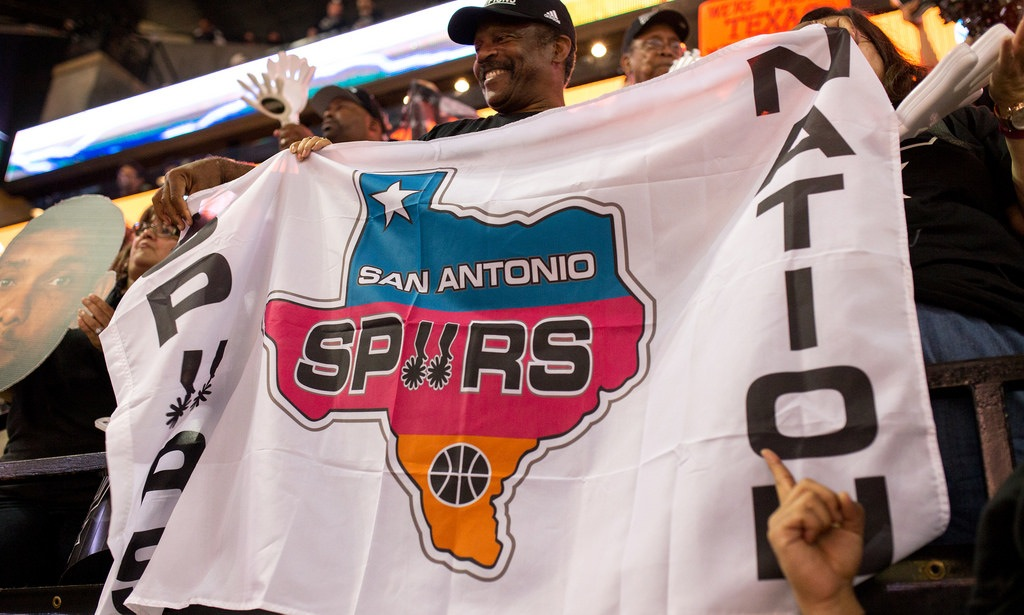 """Spurs fans hold a """"Spurs Nation"""" flag during the Game 1 of the 2014 NBA Finals. Photo by Scott Ball."""