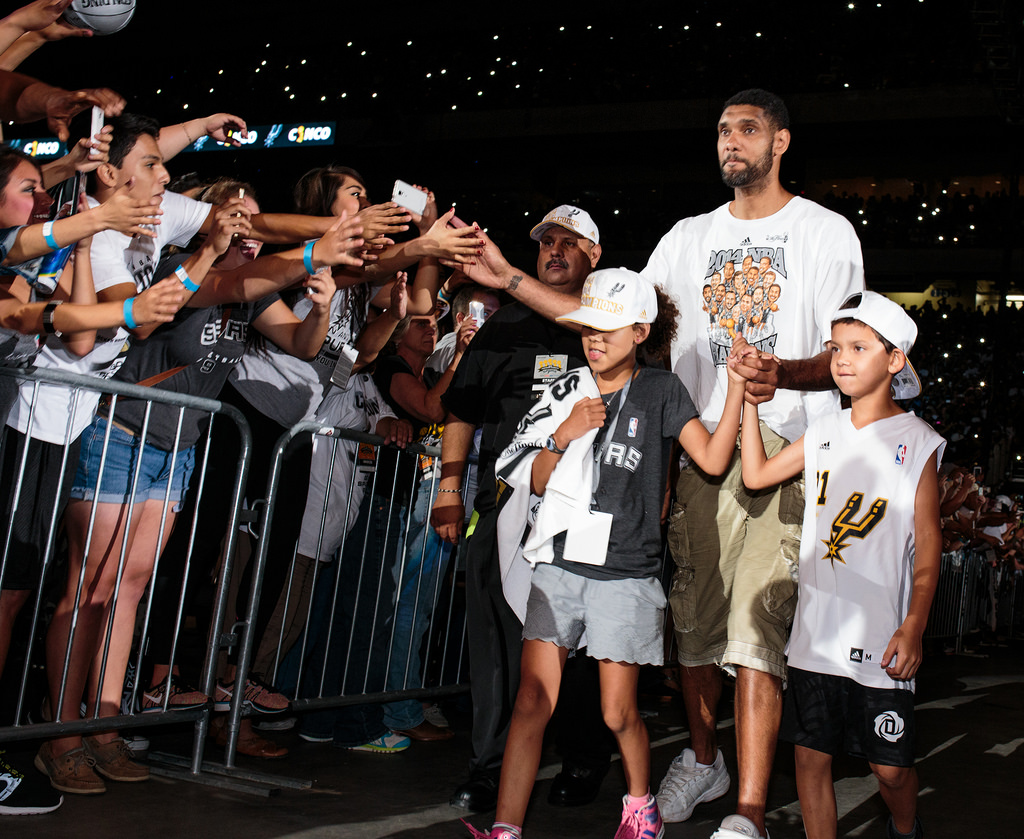 Tim Duncan and his children Sydney and Draven walk to the stage during the Spurs celebration at the Alamodome of their 2014 NBA Finals victory. Photo by Scott Ball.