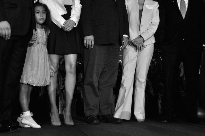 """Carina Castro shyly stands amid her parents, Julián and Erica, and others during Centro San Antonio's """"The Future of Downtown"""" luncheon. July 10, 2014. Photo by Iris Dimmick."""
