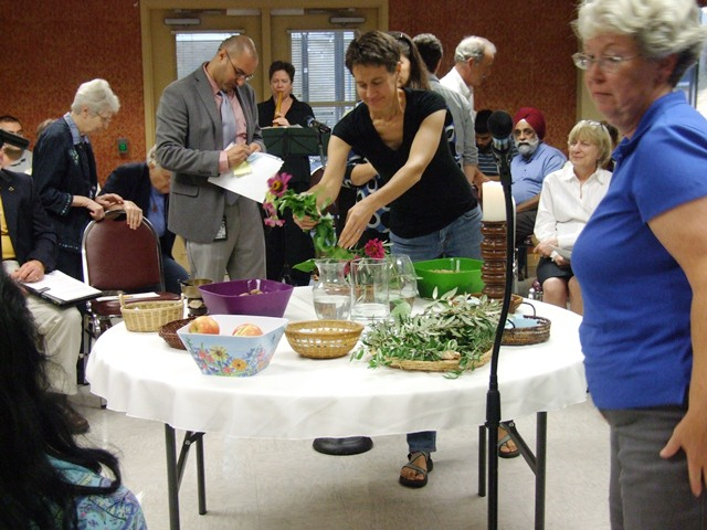 Participants, including San Antonio Mennonite Pastor Rachel Epp Miller (featured) offer tokens of nature they have brought with them as a sign of peace and mutuality during the service. Photo by Tyler Tulley.