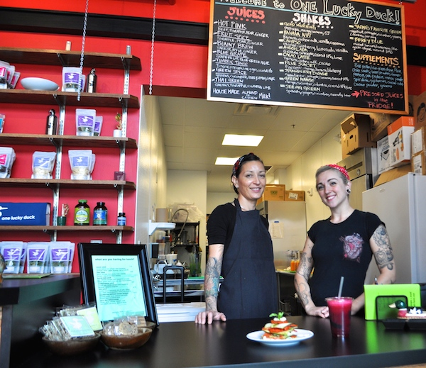 """One Lucky Duck employees and sisters Naila Safont (left) and Stella Shafer pose a photo with a """"Hot Pink"""" shake and zucchini and heirloom tomato lasangna. Photo by Iris Dimmick."""