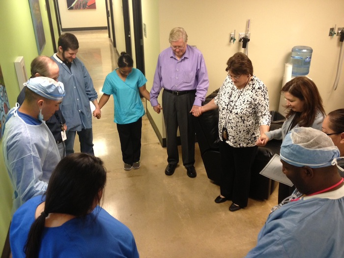 SACDC employees and volunteer staff gather in prayer before the work day begins. Executive Director Gloria Canseco stands third from left. Photo by Sarah Martinez.