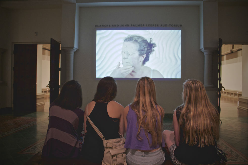 Four teenagers enjoy a video by Stephanie Patton during the McNay Art Museum's Teen Night. Photo by Tommie Ethnigton.