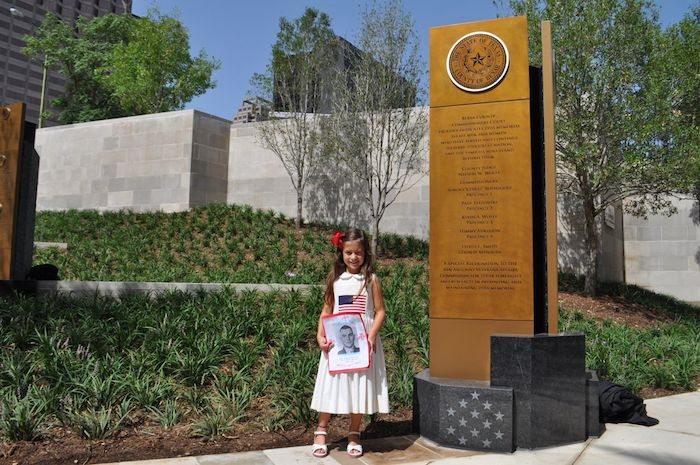 Young Tessa stands with a portrait of her veteran grandfather at the unveiling of the Medal of Honor River Portal connecting the San Antonio River to the Tobin Center for the Performing Arts July 3, 2014. Photo by Iris Dimmick.