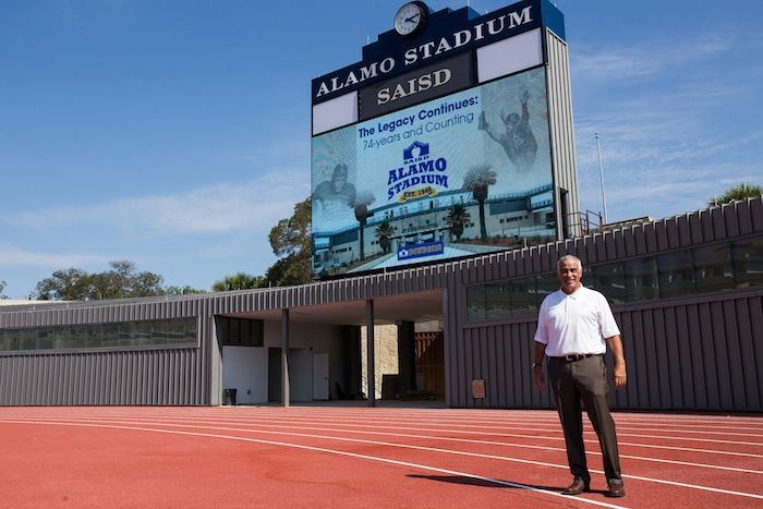 SAISD Superintendent Dr. Sylvester Perez poses in front of the new scoreboard at Alamo Stadium. Photo by Scott Ball.