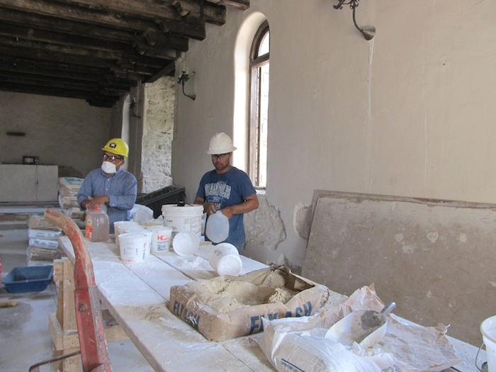 Workers prepare a special grout for injecting into the walls at Mission Espada. Photo by Carol Baass Sowa.