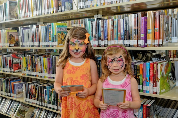 Two girls check out books during a recent event at Mission Branch Library.