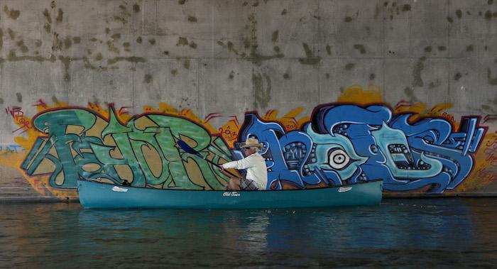 ALBUQUERQUE, NM - Jason Jones passes under a bridge with graffiti on the Rio Grande River through Albuquerque, New Mexico. AUGUST 17, 2014: CREDIT: Erich Schlegel/Disappearing Rio Grande Expedition