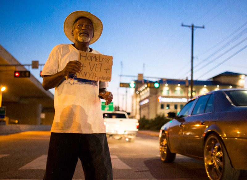 Cars pass Earl, an Armed Forces veteran, remains hopeful one will stop at a green light and help him out. He says about 35 out of 100 do. Photo by Scott Ball.