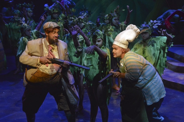 Farmers Boggis (Edwin Vega) and Bunce (Andrew Craig Brown) sneak away from Farmer Bean to stuff themselves with food into a forest of trees (Children's Chorus of San Antonio). Photo by Karen Almond.