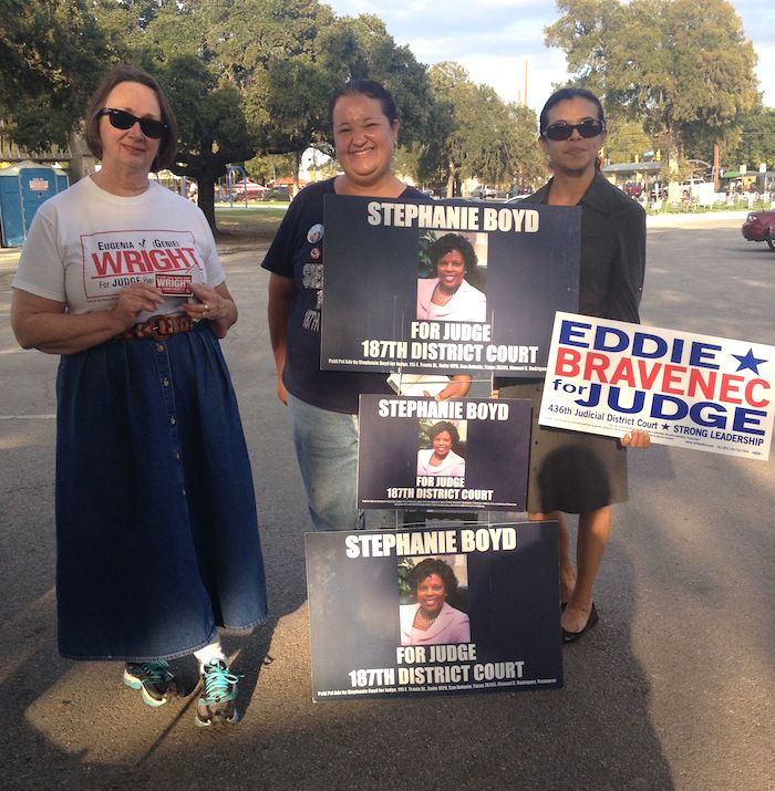 """From left: County Court #7 Judge Eugenia """"Genie"""" Wright, volunteer Jessica Barraza, and volunteer Theresa Canales spread campaign signs at Lion's Field. Photo by Robert Rivard."""