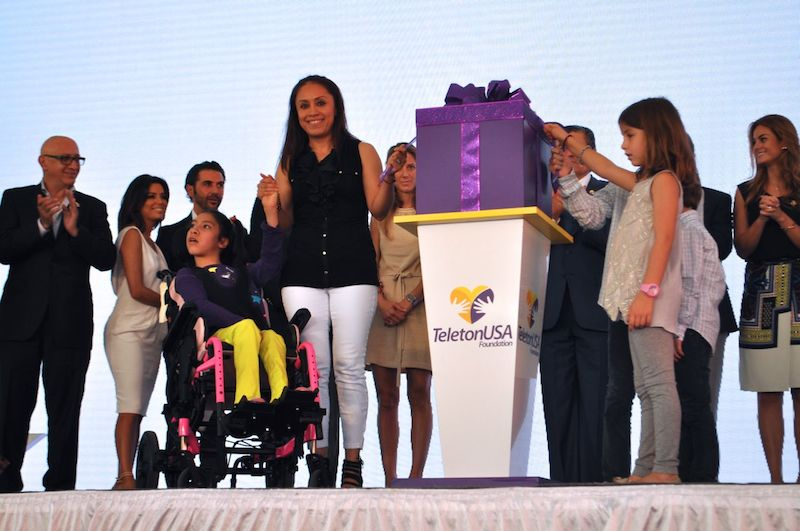 Teletón and Univision representatives and families join Sofia and Iris Urrútia as they open their present, a TeletónUSA plaque that officially opens CRIT USA. Photo by Iris Dimmick.