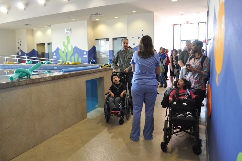 Families tour the CRIT USA facilities which includes a large therapy pool for children with disabilities. Photo by Iris Dimmick.