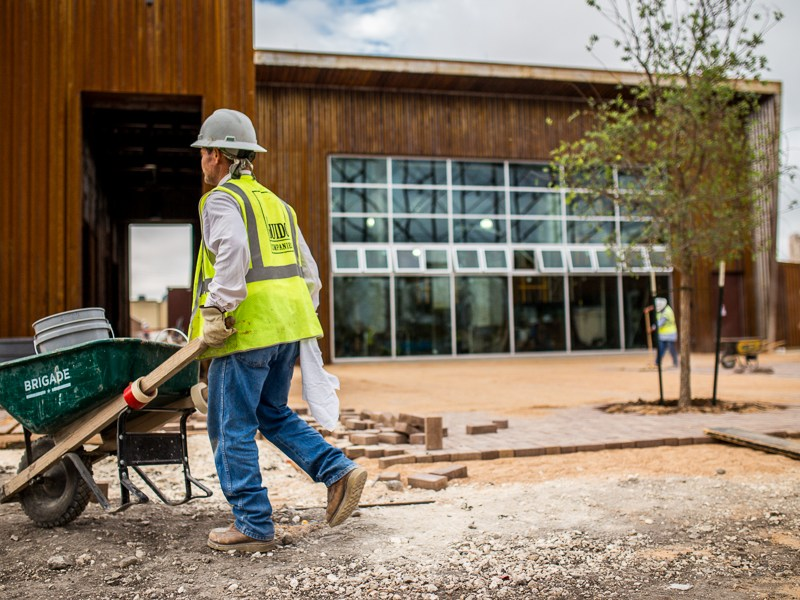 A construction worker passes where trees line the beer garden at Alamo Beer Company. Photo by Scott Ball.