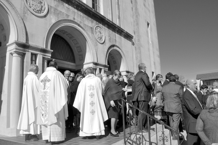 Friends and family of Elvira Munguia Cisneros (1924 - 2014), embrace on the steps of the Basilica of the National Shrine of the Little Flower after the Catholic funeral Mass. Photo by Iris Dimmick.