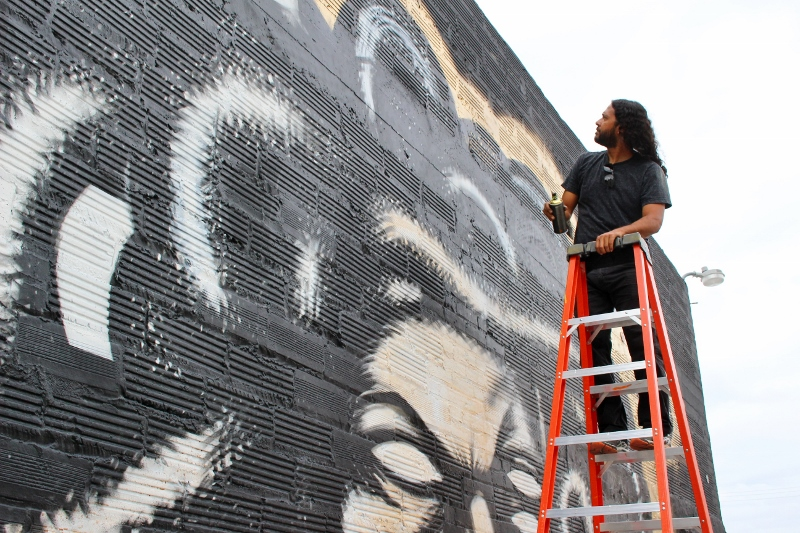 Armando Lerma works on the Date Farmers mural. Photo by Page Graham.