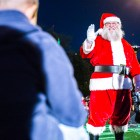 Santa Claus waves to a child at the H-E-B Tree Lighting Ceremony. Photo by Scott Ball.