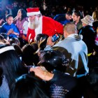 Santa Claus surrounded by parents and children at the H-E-B Tree Lighting Ceremony. Photo by Scott Ball.