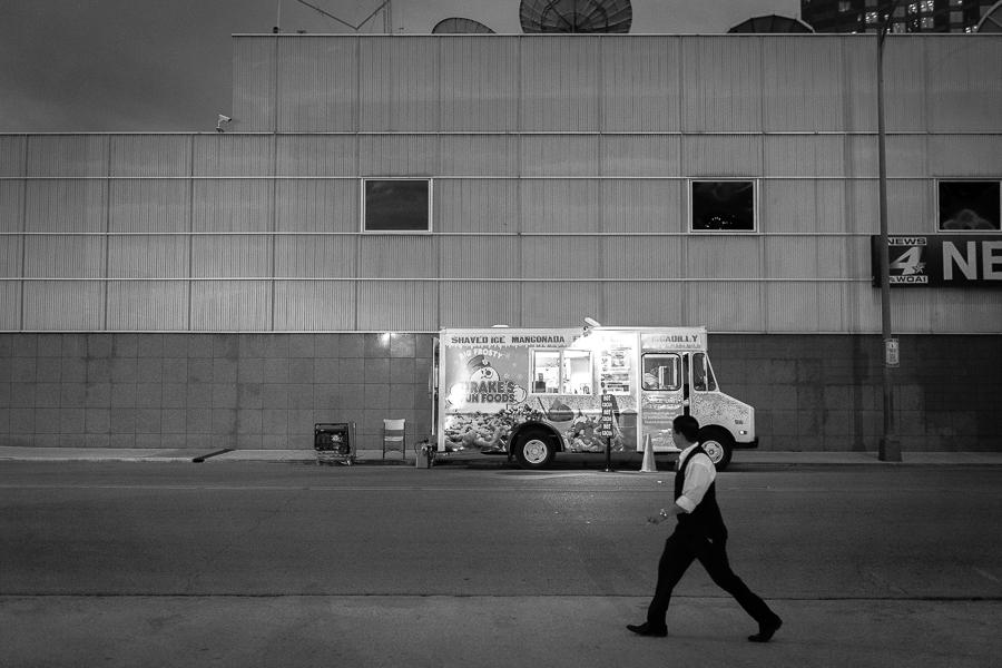 A man walks down the sidewalk while looking at a food truck at Luminaria. Photo by Scott Ball.