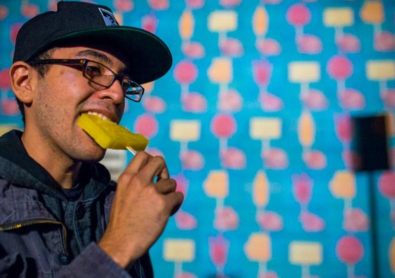Edward Flores eats a paleta in front of artist Gary Garay's paleta covered wall at Luminaria. Photo by Scott Ball.