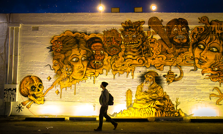 A man walks by one of the many murals at Luminaria. Photo by Scott Ball.