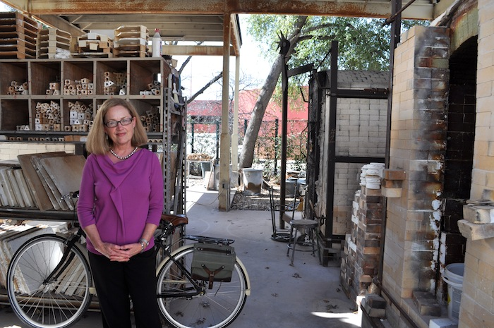 Southwest School of Art President Paula Owen poses for a photo on the school's kiln patio. Photo by Iris Dimmick.