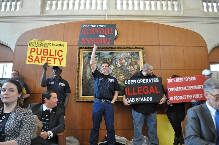 Uber supporters look on as traditional taxi company drivers hold signs in protest of changes to the Vehicle for Hire Ordinance. Photo by Iris Dimmick.
