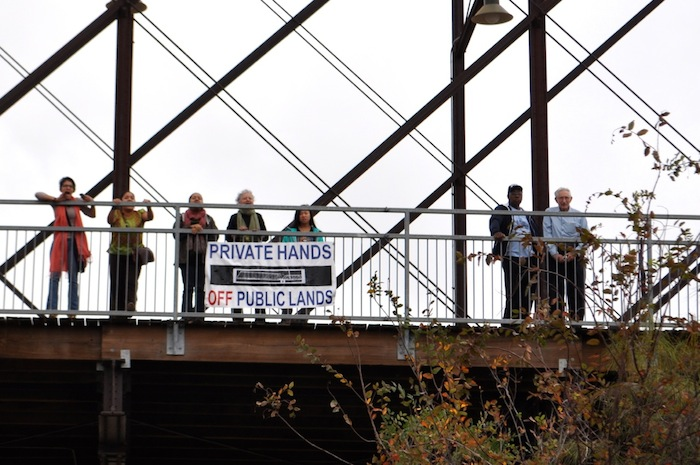 A handful of protestors (left) shout and chant from the Hays Street Bridge during the ribbon-cutting ceremonies at the Alamo Beer Company brewery.