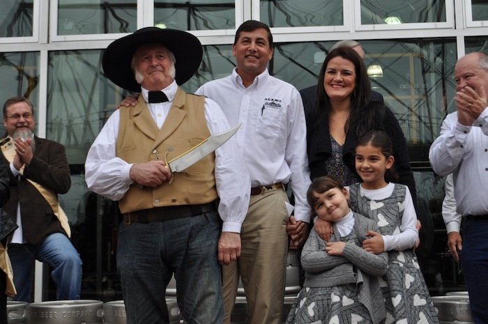 Alamo Beer Company Founder and President Eugene Simor stands with his family and historic reenactor Mike Waters after cutting of the ceremonial ribbon to mark the beginning of production. Photo by Iris Dimmick.