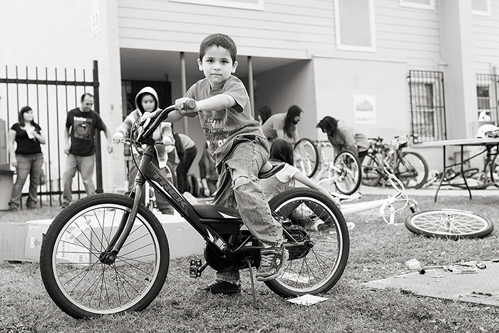 Kids test out their new bikes after assembly during the Earn-A-Bike Christmas at Cassiano Homes. Photo by Rachel Chaney.