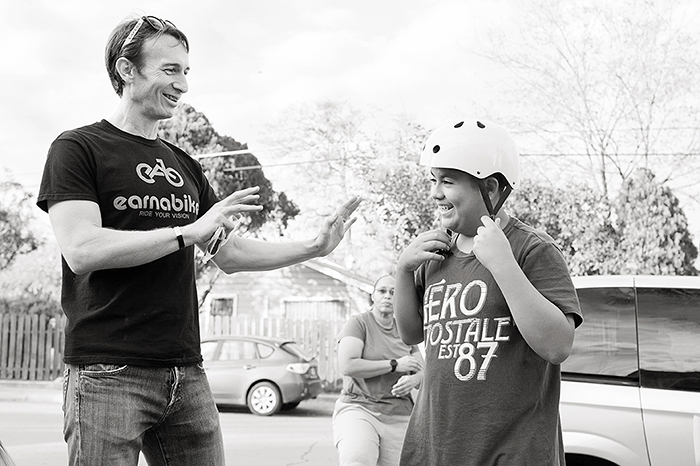 Cristian Sandoval talks helmets during the Earn-A-Bike Christmas at Cassiano Homes. Photo by Rachel Chaney.