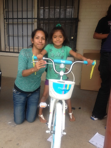 Aaliyah, age 7, and her mom pose with Aaliyah's completed bike, on Day One of the Earn-a-Bike Christmas program. Photo by Lily Casura.