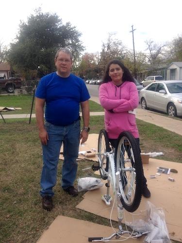 Earn-a-Bike volunteer Steve Abrams, who lost his grandson in a tragic bike accident, helps Desiree Juarez, 14, earn her bike. Photo by Lily Casura.