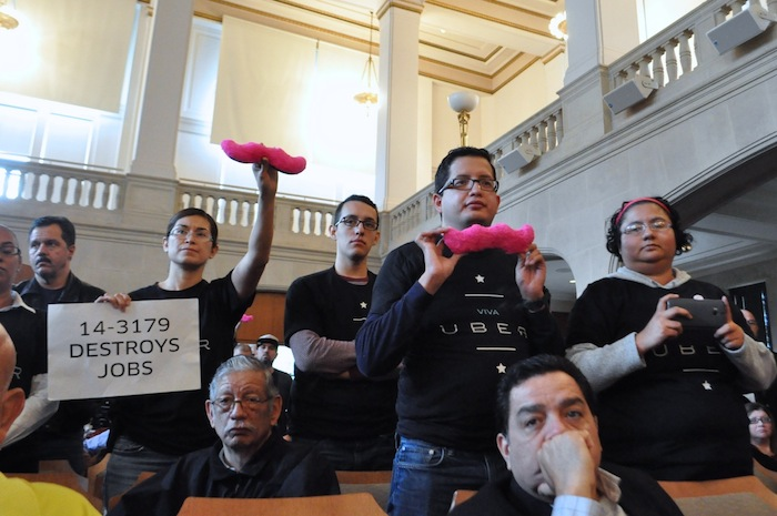 Rideshare advocates stand in support of Lyft and Uber during a City Council meeting that resulted in approval of strict rideshare regulation. Photo by Iris Dimmick.