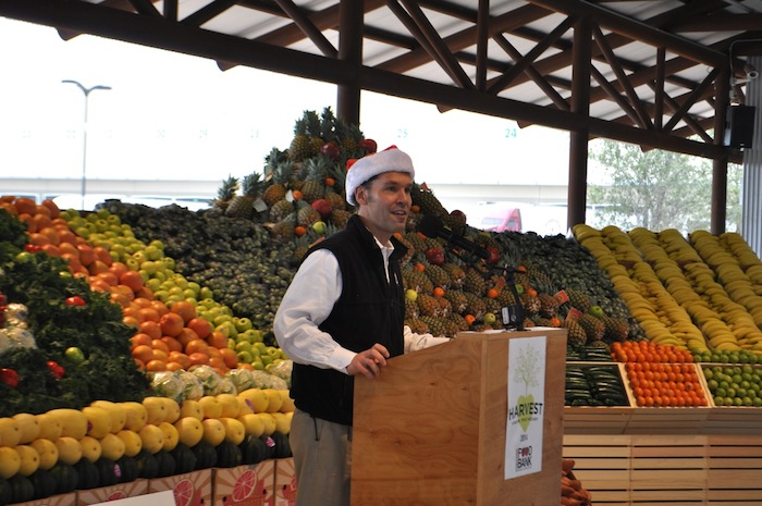 San Antonio Food Bank President and CEO Eric Cooper speaks in front of the huge pile of fresh produce donated by H-E-B, a sampling of the 2.5 million pound donation from the grocery chain. Photo by Iris Dimmick.