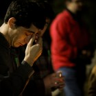 A young man bows his head during a candlelight vigil on the one year anniversary of Cameron Redus' death. Photo by Scott Ball.