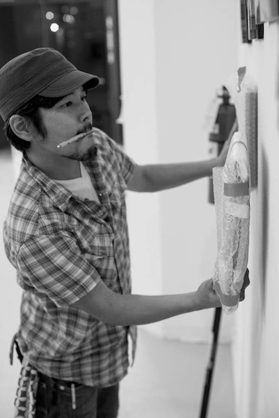 Artist Mat Kubolnstall prepares the AME Collaborative space for the OPEN Pop-up market downtown. Photo by David Rangel.
