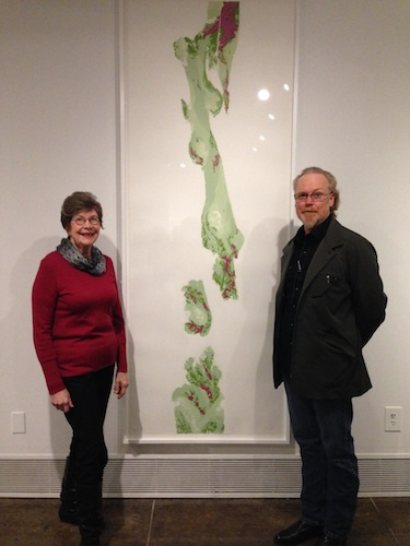 Janet Flohr and Gary Nichols stand with a reduction print by Rajani Shettar. Photo by Wendy Weil Atwell.