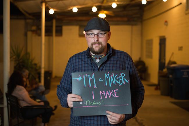 "Mark Barnett, one of Make San Antonio's founders, holds a ""I'm a Maker"" sign during Make San Antonio's Makevember event. Photo by Ruben E. Reyes."