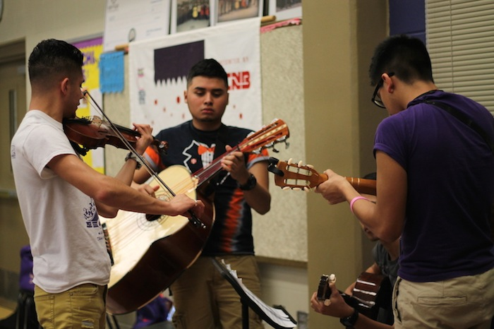 (From left) Oscar Garza, Alexis Reyes and Jude Perez come to help out a less experienced mariachi player memorize his music. Photo by Amanda Lozano.